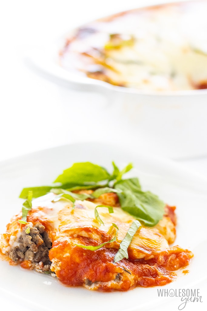lasagna without noodles, on a plate with basil and casserole dish in the background