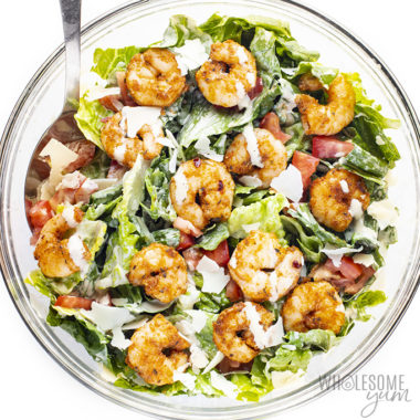 shrimp caesar salad recipe in a bowl with dressing