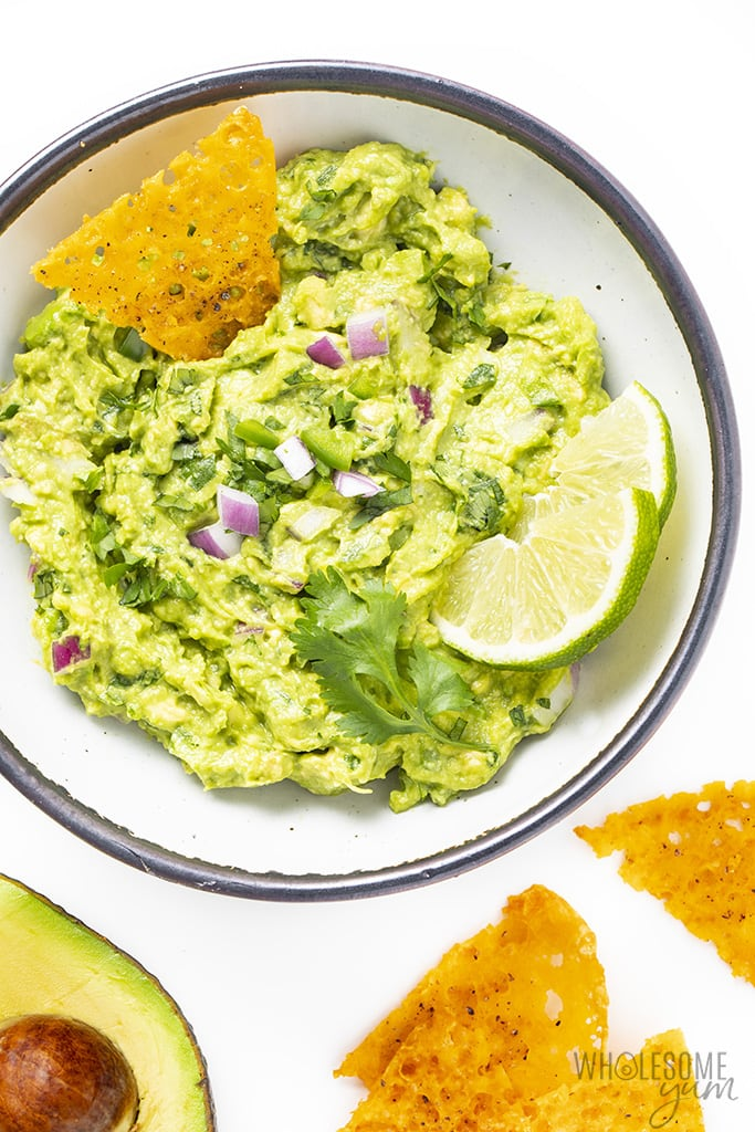 best guacamole recipe in a bowl with limes and cheese crisps