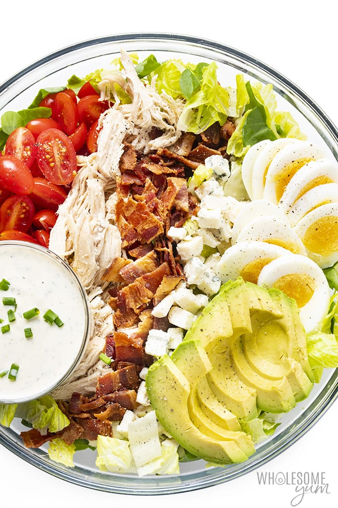 Homemade cobb salad in a large bowl with ranch dressing in a ramekin