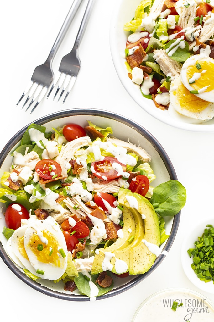 Healthy cobb salad in serving bowls drizzled with dressing