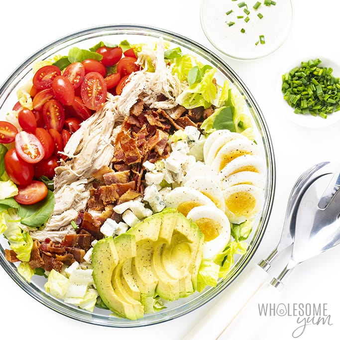 Easy cobb salad dressing recipe in a bowl with ranch dressing, servers, and chives