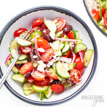Greek salad in a small bowl with a fork