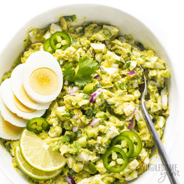 overhead shot of avocado egg salad in a bowl with sliced eggs and lime on the side