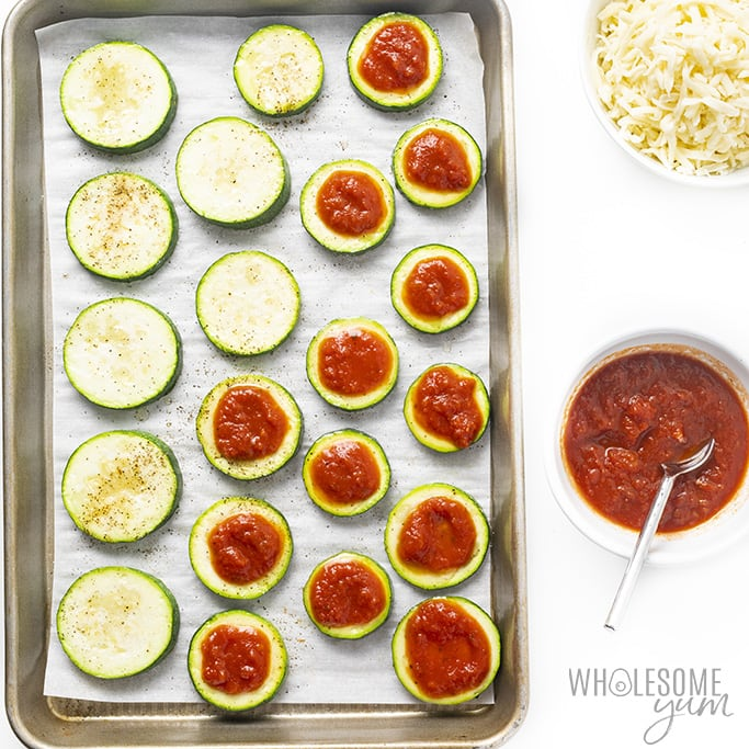 topping mini zucchini pizzas with sauce and cheese