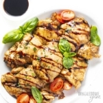 Overhead view of balsamic chicken thighs on a platter with balsamic drizzle and basil and tomato
