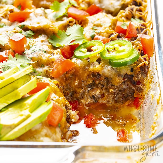 Are Bell Peppers Keto? Overhead view of Mexican ground beef casserole in a casserole dish divided into 9 servings with cilantro, jalapenos, and avocado slices and a slice removed