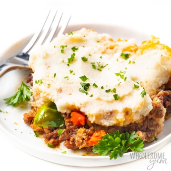 Close-up view of keto shepherds pie on a plate with parsley and a fork