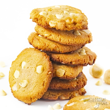 Stack of keto white chocolate macadamia nut cookies with white chocolate chips scattered