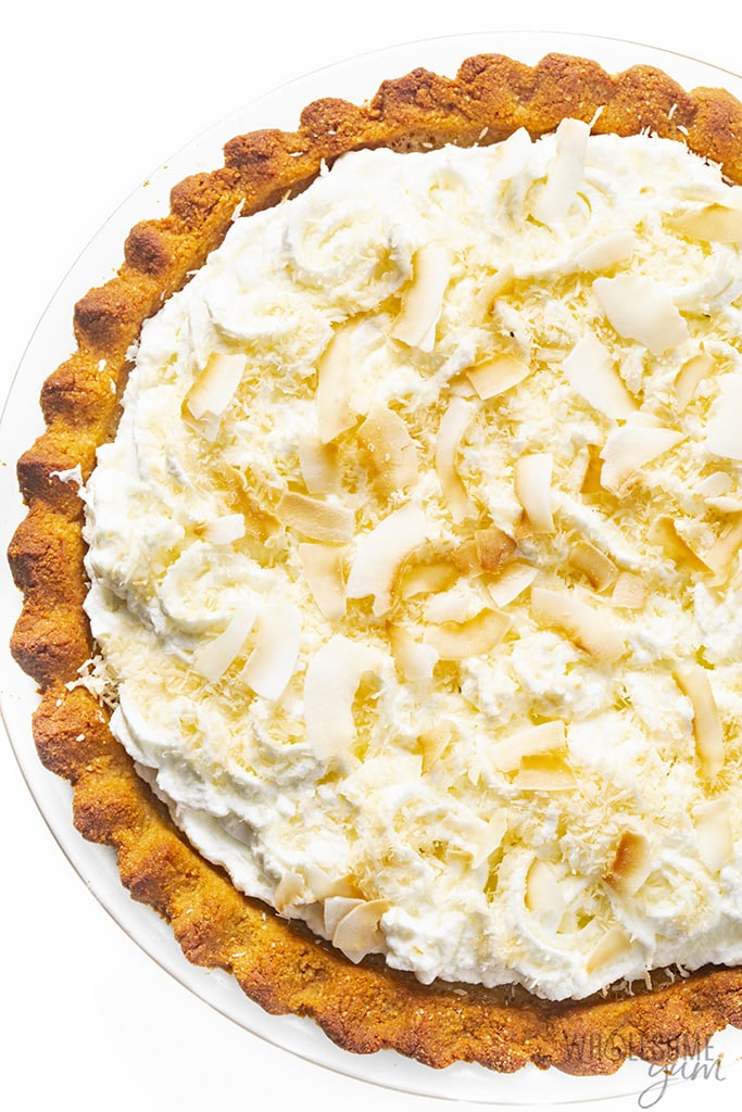 Keto friendly coconut cream pie topped with cream and coconut flakes