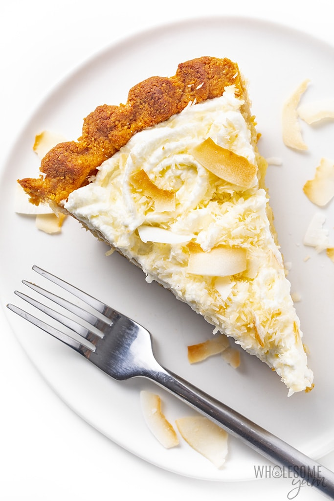 Slice of sugar-free coconut cream pie on a plate with a fork and coconut flakes