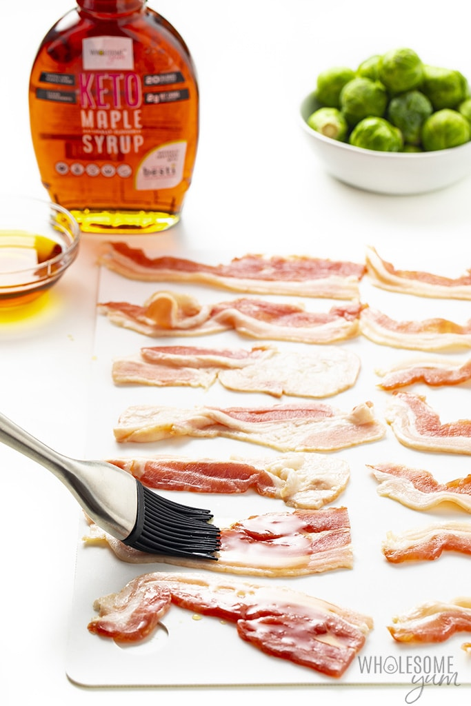 Bacon slices on a cutting board being brushed with Keto Maple Flavored Syrup and Brussels sprouts in the background