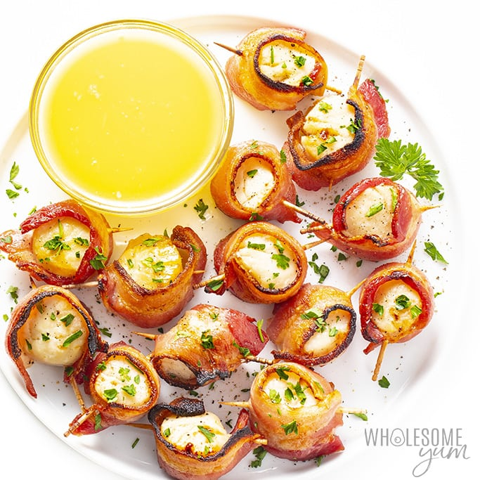 Broiled bacon wrapped scallops on a plate with butter and parsley