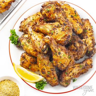 Lemon pepper wings stacked on a white plate with a lemon wedge