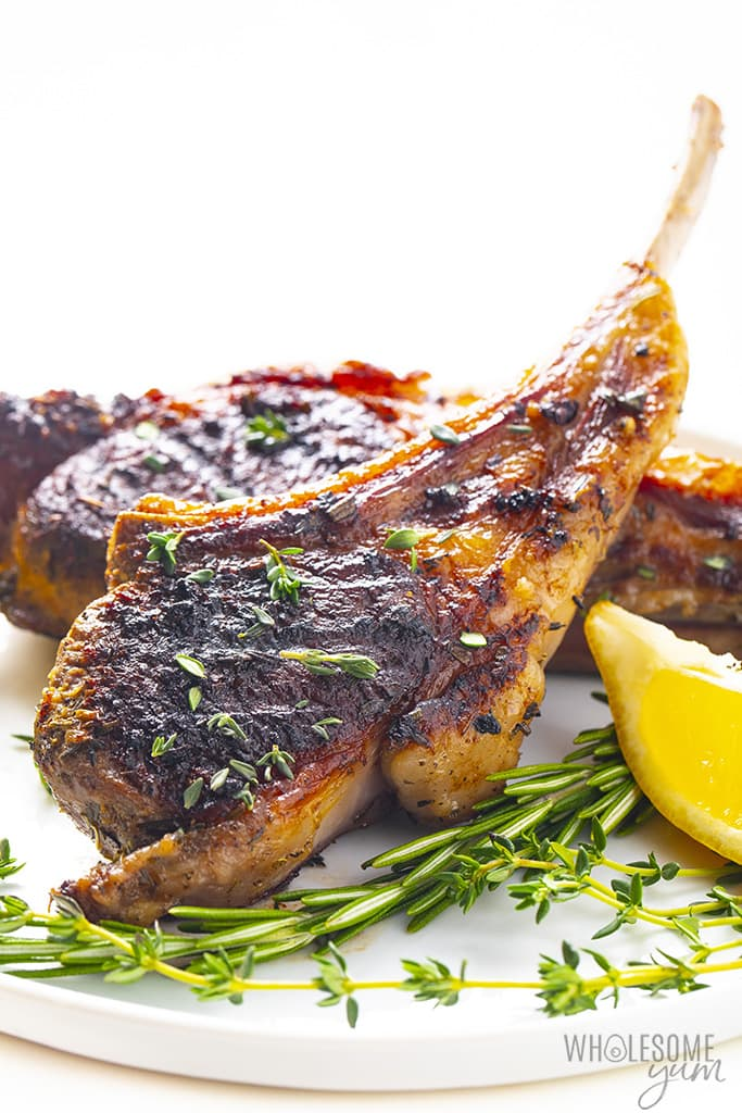 Lamb chops plated with herbs and lemon wedge