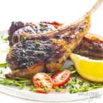 Oven baked lamb chops on a plate with lemon wedges and sliced grape tomato