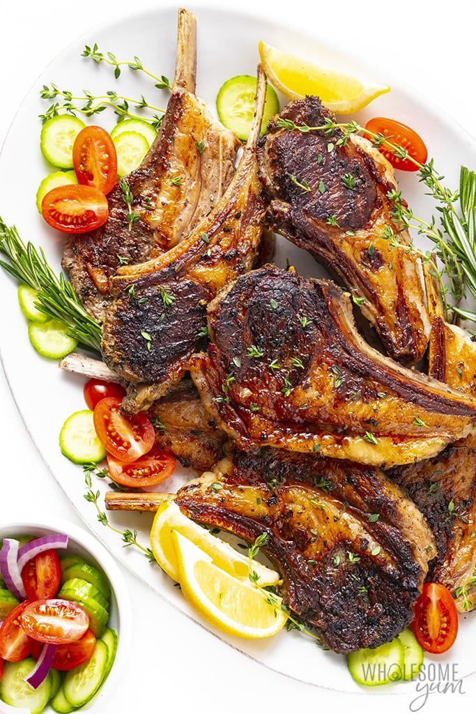 Roasted lamb chops on a platter with lemon, rosemary, tomatoes, and cucumbers