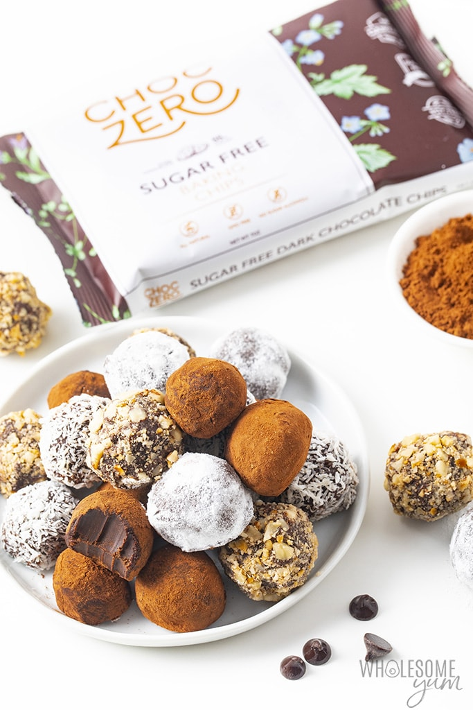 Keto chocolate truffles plated next to a bag of ChocZero dark chocolate chips