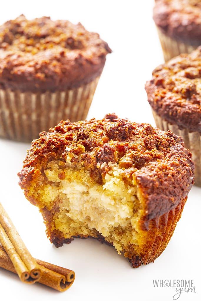 Four cinnamon cream cheese keto muffins with cinnamon sticks