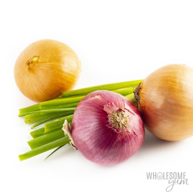 Two yellow onions, one red onion, and a bundle of green onions