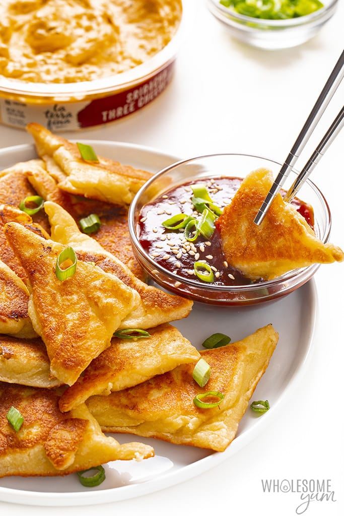 Keto crab rangoon being dipped in sweet and sour sauce with chopsticks