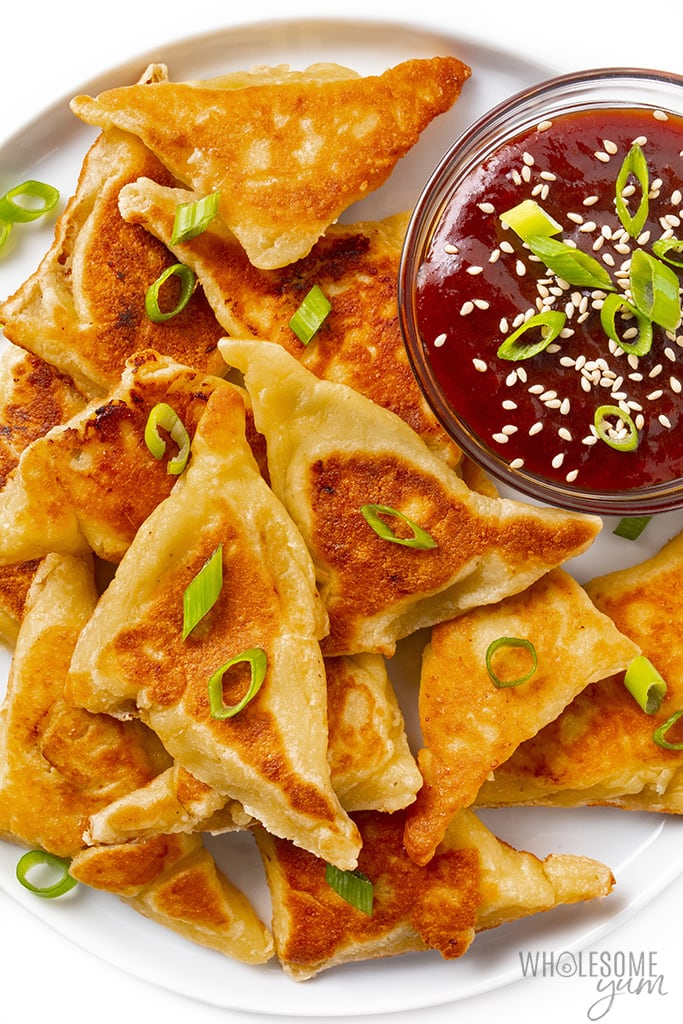 Close up of keto wontons on a plate with sauce