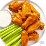 Buffalo chicken wings on a plate with celery and blue cheese