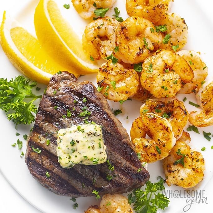 Steak and shrimp on a plate with lemon