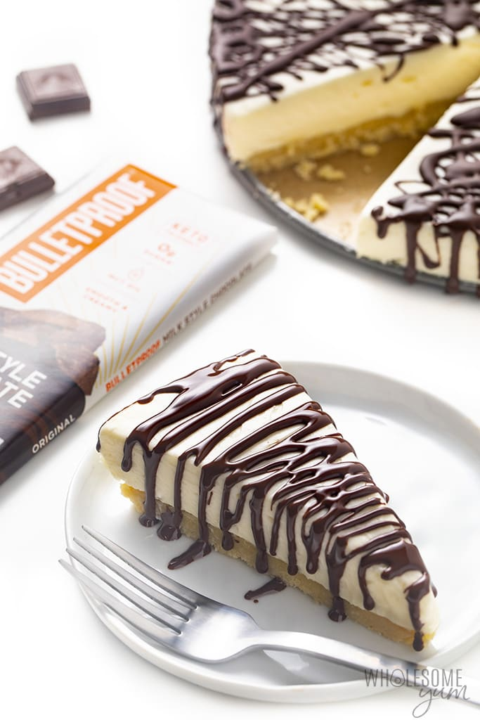 No bake cheesecake slice on a plate with chocolate bar in the background