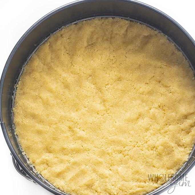 Keto crust for no bake cheesecake pressed into springform pan