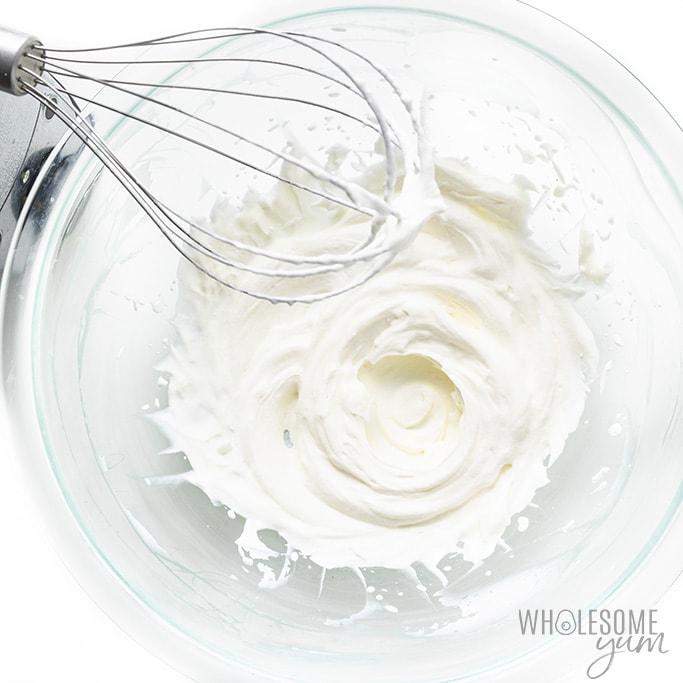 Beaten heavy cream in a glass bowl