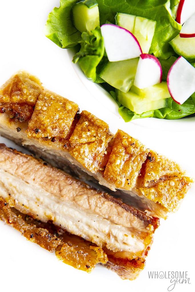 Pork belly sliced next to salad