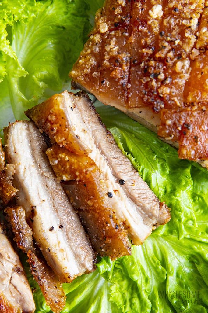 Sliced pork belly on a bed of lettuce