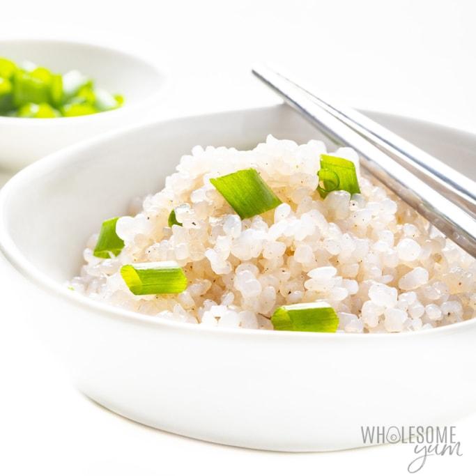 Bowl of keto shirataki rice with green onions on top