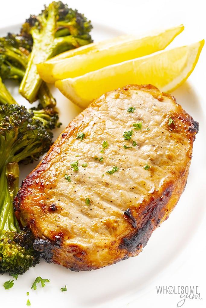 Air fryer boneless pork chop on a plate with broccoli