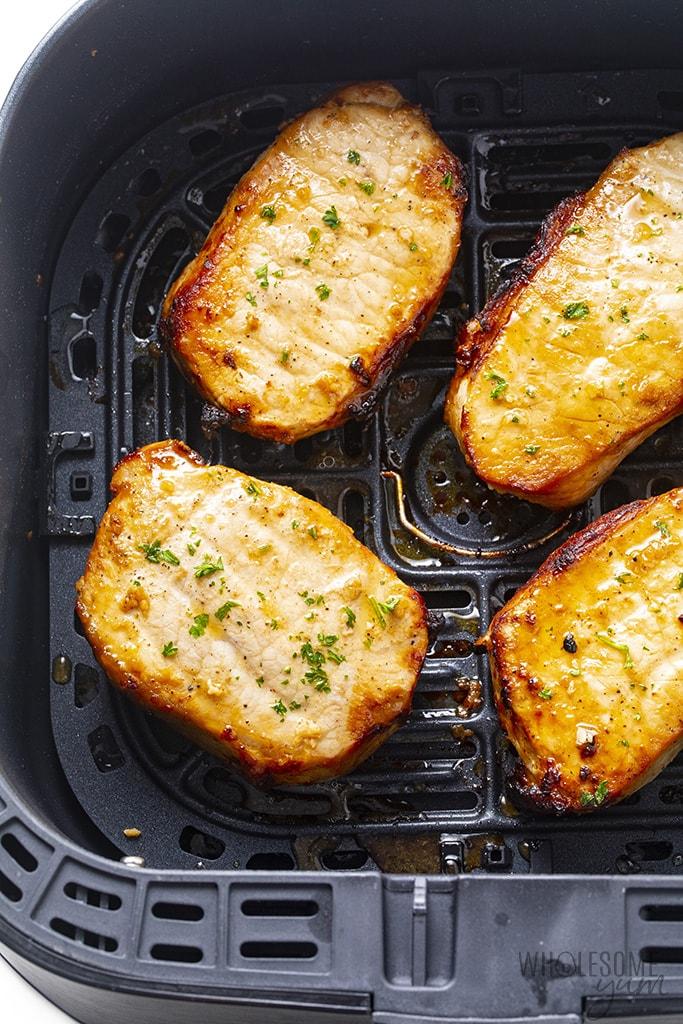 Juicy cooked pork chops in air fryer basket
