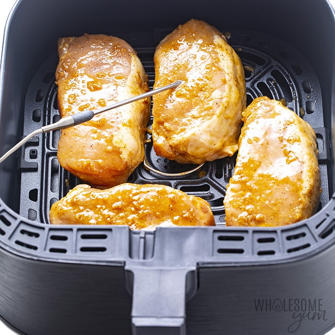 air fryer thick pork chops in air fryer basket with temperature probe