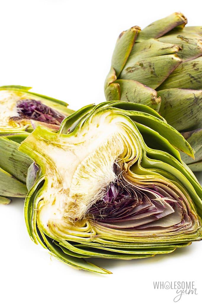 Keto artichokes, one sliced in half