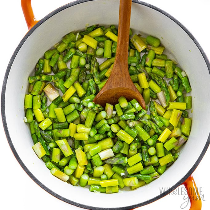 Sauteed asparagus in a red pot
