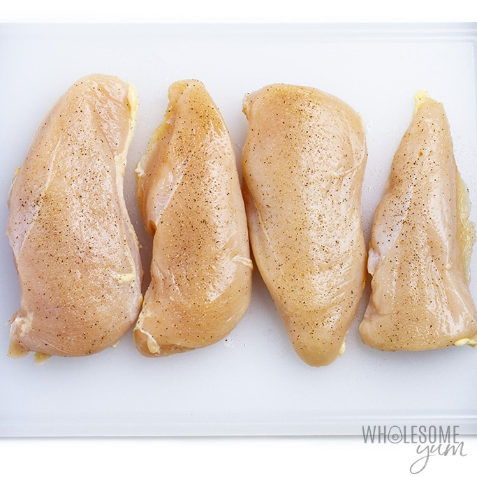 Chicken breast on a cutting board with salt and pepper