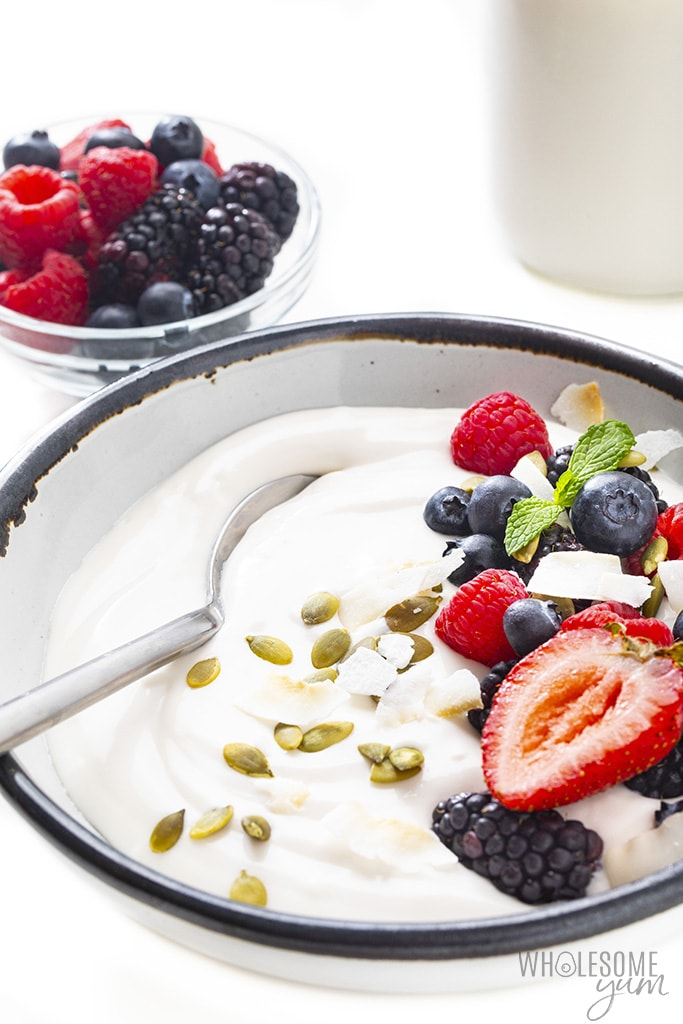 Coconut yogurt recipe in a bowl next to a bowl of berries