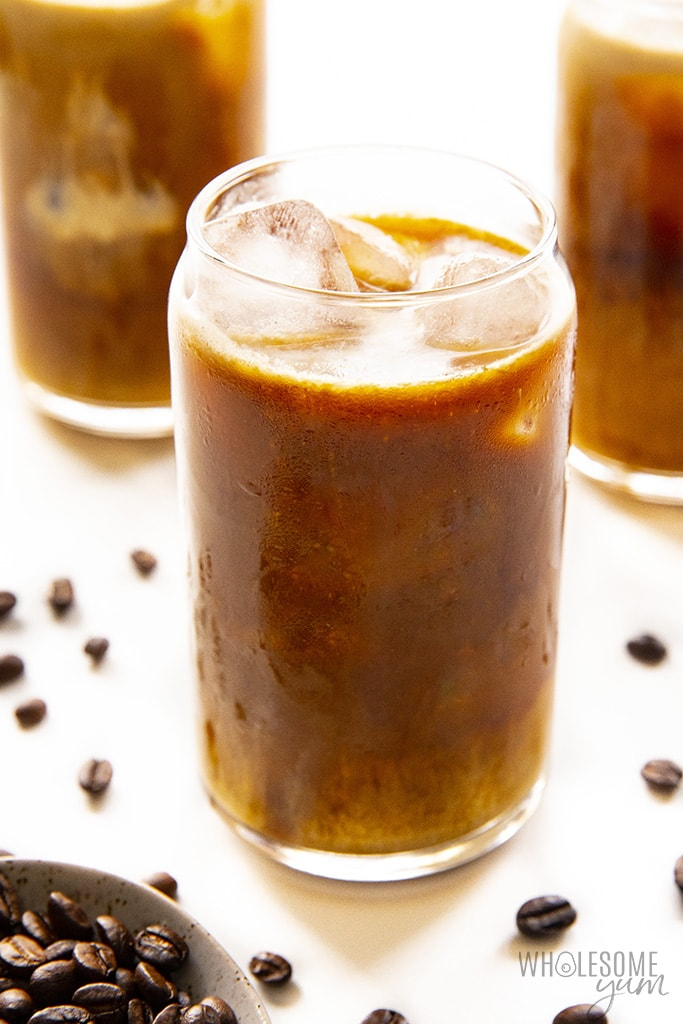Glasses of keto iced coffee next to scattered coffee beans
