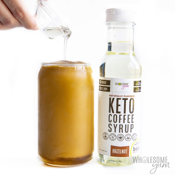 Low carb iced coffee in a glass with hand pouring keto coffee syrup into glass