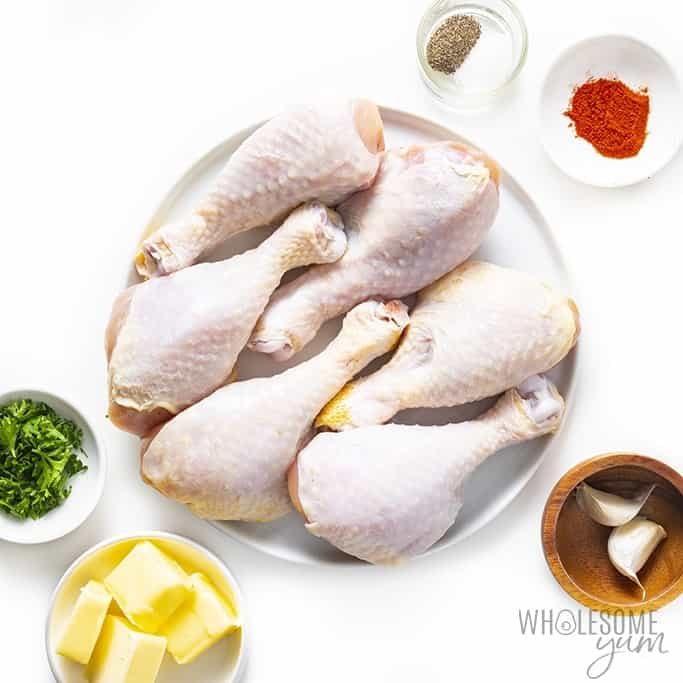 Ingredients for air fryer chicken drumsticks on plates and in bowls