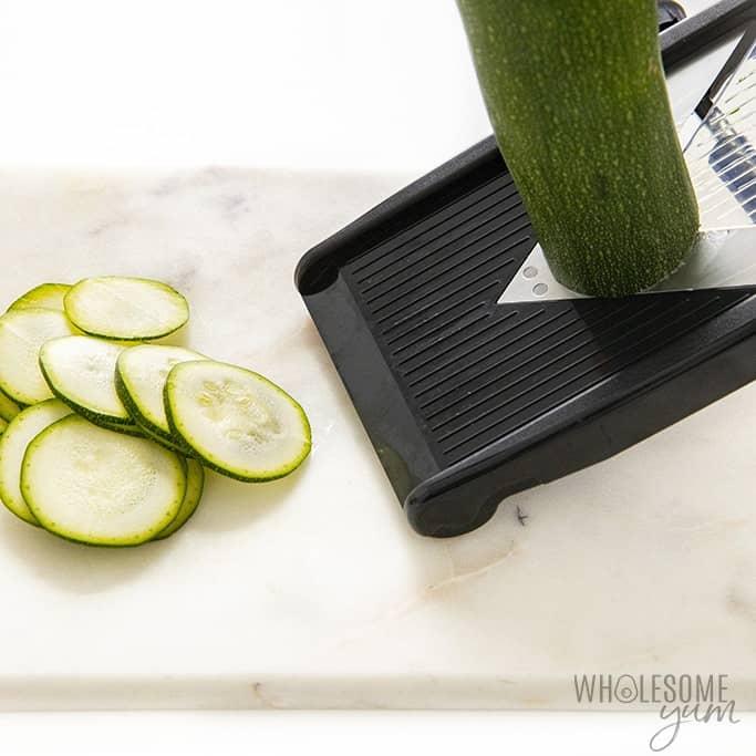 Slicing zucchini with a mandolin slicer