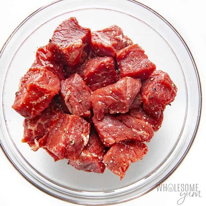 Raw steak cubes for steak bites recipe seasoned with salt and pepper