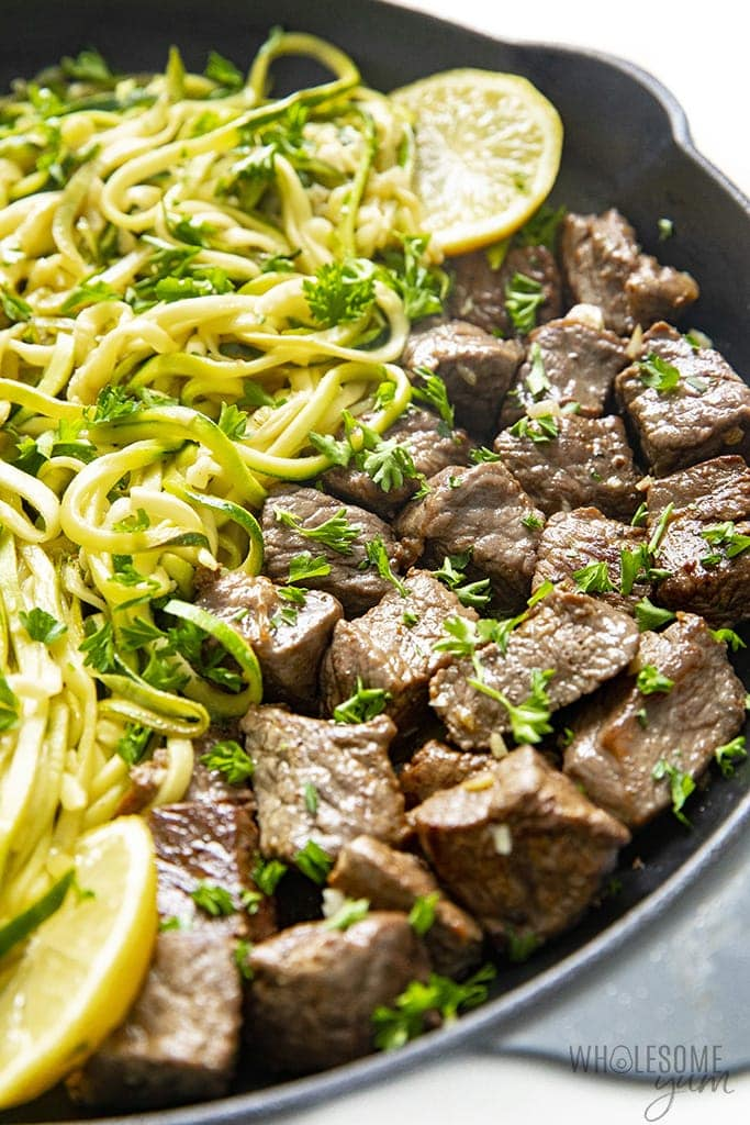 Garlic butter steak bites in a skillet with zoodles
