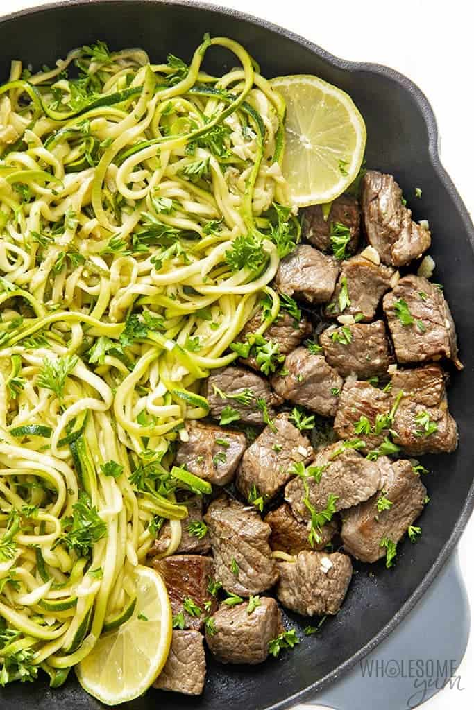 Garlic butter steak bites with zucchini noodles in skillet with lemon slice