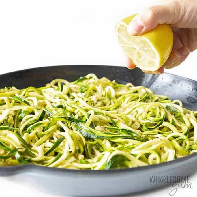 Zucchini noodles in a pan with lemon squeezed over the top