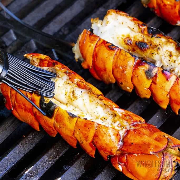 Brushing lobster tail with butter sauce on grill
